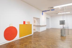 Zdjęcie sali o białych ścianach. Na ścianach po lewej dość duże figury geometryczne: czerwone koło, żółty prostokąt, a także małe niebieskie prostokąty na suficie. Po prawej na drewnianej podłodze instalacja przypominająca konstrukcję budynku.