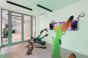 Zdjęcie białego pomieszczenia z przeszkloną ścianą. Na środku widać dwie instalacje. Pierwsza przypomina zielono-pomarańczową ciecz, a druga, zielono-czarna ma kolce. Na ścianie po prawej wiszą dwa monitory.
