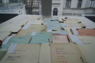 Na blacie stołu rozłożone są liczne teczki z tektury o różnych kolorach. Widać na nich odręcznie pisane tytuły i adnotacje. W tle panoramiczny widok za oknem: jasna fasada i dziedziniec Muzeum Sztuki w Łodzi.
