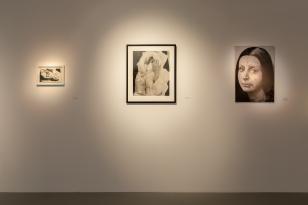 Wnętrze sali wystawienniczej; widok na wprost na białą ścianę, na której zawieszono trzy  czarno-białe zdjęcia; po prawo kobiecy portret, pośrodku kobietę w wacie, po lewo małą oprawioną fotografię.