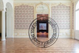Kolorowe poziomo zorientowane zdjęcie sali wystawienniczej; widok na wprost; na pierwszym planie metalowa rzeźba-napis w formie okręgu: A GUIDING STAR ON OUR JOURNEY TO TRANSFORM; w głębi widok na projekcję dziejącą się w kolejnej sali.