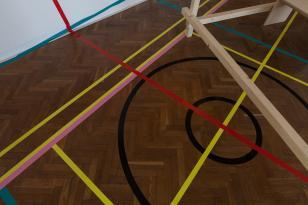 Kolorowe poziomo zorientowane zdjęcie sali wystawienniczej; 7/8 zajmuje widok parkietu przypominającego boisko, bo  wyklejonego czarnymi okręgami i żółtymi i niebieskimi liniami, które ukośnie wchodzą na widoczny fragment białej ściany.