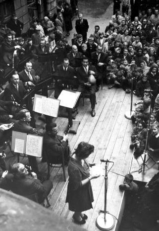 Teresa Kmiecińska-Kaczmarek (Dział Naukowo-Oświatowy) ogłasza wyniki konkursu Zgaduj-Zgadula, w tle orkiestra Edwarda Ciukszy