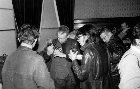 Poczęstunek w sali odczytowej ms, z fotografiami malarz Leon Tarasiewicz, żona Mariusza Kruka, Mariusz Kruk, w głębi pierwszy z prawej fotograf Robert Laska